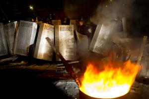 Riot police officers prepare to break through a barricade while trying to displace pro-European Union activists from the Ukrainian presidential administration building in Kiev, Ukraine, Tuesday, Dec. 10, 2013.