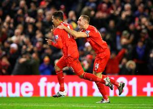 LIVERPOOL, ENGLAND - JANUARY 13:  Roberto Firmino (L) of Liverpool celebrates scoring his team's second goal with his team mate Jordan Henderson (R)  during the Barclays Premier League match between Liverpool and Arsenal at Anfield on January 13, 2016 in Liverpool, England.  (Photo by Alex Livesey/Getty Images)