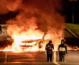 A car burns on the rail tracks at Antrim Road during disturbances in Lurgan on Sunday night