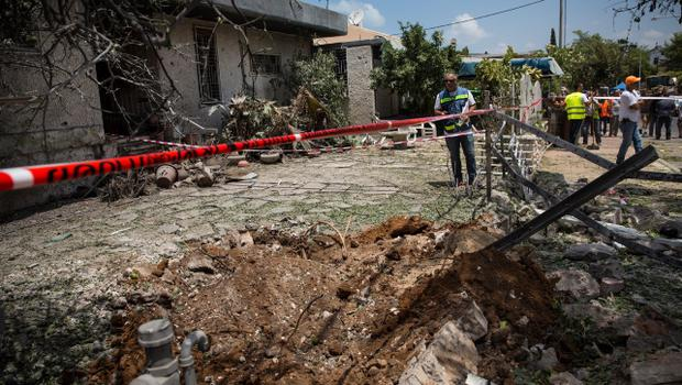 "ASHDOD, ISRAEL - JULY 15:  A crater from a Hamas rocket is seen in the front yard of a home on July 15, 2014 in Ashdod, Israel.  As operation 'Protective Edge"" enters it's eighth day of airstrikes by the Israel Defense Forces (IDF) across the Gaza Strip, Egypt has this morning tabled a ceasefire agreement proposing a halting of fighting starting at 9am. Once violence has ceased, the proposal calls for Israel to open a border crossing into Gaza to allow the movement of goods and people. Israel has accepted the Egyptian proposal for a truce, however it is thought Hamas has rejected the deal.  (Photo by Andrew Burton/Getty Images)"