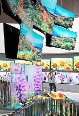 BERLIN, GERMANY - SEPTEMBER 03:  A visitor looks at 4K SUHD curved televisons at the Samsung stand during a press day at the 2015 IFA consumer electronics and appliances trade fair on September 3, 2015 in Berlin, Germany. The 2015 IFA will be open to the public from September 4-9.  (Photo by Sean Gallup/Getty Images)