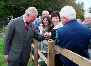 The Prince of Wales meets well-wishers outside the YMCA Londonderry at Drumahoe and Eglinton Community Centre, in Londonderry, during a visit to communities hit by the summer's flash floods. Brian Lawless/PA Wire