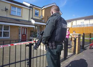 A police officer outside the house in which the body was found