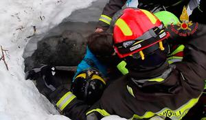"""A handout picture released on January 20, 2017 by the Vigili del Fuoco shows a child (C) being rescued from the Hotel Rigopiano, near the village of Farindola, on the eastern lower slopes of the Gran Sasso mountain, engulfed by a powerful avalanche a day before.  """"AFP PHOTO / VIGILI DEL FUOCO"""
