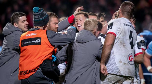 Ulster players congratulate captain Billy Burns after his try.