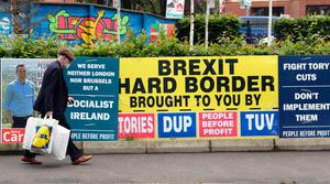 Pedestrians walk past election posters in west Belfast on June 8, 2017 as Britain votes in the general election. Polls opened in Britain today in an election Prime Minister Theresa May had expected to win easily but one that has proved increasingly hard to predict after a campaign shadowed by terrorism. / AFP PHOTO / Paul FAITHPAUL FAITH/AFP/Getty Images