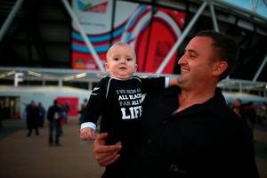 A young New Zealand fan shows his support outside the ground before the Rugby World Cup match at the Olympic Stadium, London
