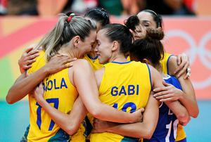 TOPSHOT - Brazilian players celebrate after winning the women's qualifying volleyball match between Brazil and Argentina at the Maracanazinho stadium in Rio de Janeiro on August 8, 2016, during the 2016 Rio Olympics. / AFP PHOTO / Johannes EISELEJOHANNES EISELE/AFP/Getty Images
