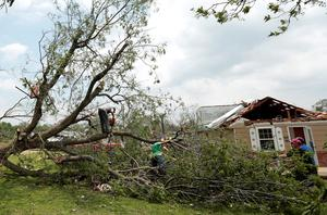 SHAWNEE, OK - MAY 20:  Volunteers chain saw a fallen tree knocked down by a tornado May 20, 2013 near Shawnee, Oklahoma. A series of tornados moved across central Oklahoma May 19, killing two people and injuring at least 21. (Photo by Brett Deering/Getty Images)