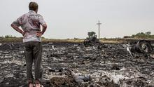 A man looks at debris from an Malaysia Airlines plane crash on July 18, 2014 in Grabovka, Ukraine. Malaysia Airlines flight MH17 travelling from Amsterdam to Kuala Lumpur has crashed on the Ukraine/Russia border near the town of Shaktersk. The Boeing 777 was carrying 280 passengers and 15 crew members. (Photo by Brendan Hoffman/Getty Images)