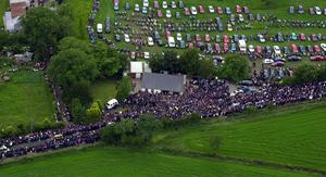 PACEMAKER BELFAST 7/7/2000 Thousands of mourners follow the coffin of Racing legend Joey Dunlop at his funeral in Ballymoney this afternoon. Joey's hearse is on the left of the screen. PHOTO MARTY WRIGHT/PACEMAKER