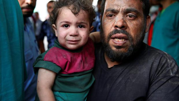 A Palestinian carries a wounded boy in the emergency room of Shifa hospital in Gaza City, northern Gaza Strip, Sunday, July 20, 2014. Hundreds of panicked residents fled a Gaza City neighbourhood which they say has come under heavy tank fire from Israeli forces. (AP Photo/Lefteris Pitarakis)