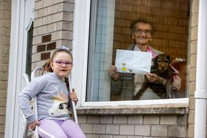 Eileen McCormick in Belfast with her dog Honey holding a letter she received from Josie Carson, aged 6, on Tuesday March 24, 2020. The six-year-old west Belfast girl has told her 90-year-old neighbour she will miss her as she stays at home during the coronavirus outbreak. Liam McBurney/PA Wire