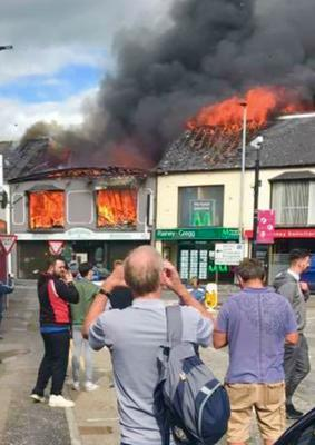 Passers-by watch as the shops go up in flames on Broughshane Street in Ballymena yesterday