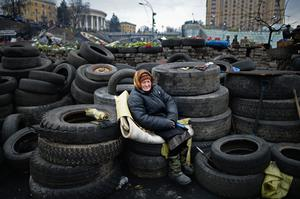 An elderly woman sits on tyres at a barricade in independence square on February 23, 2014 in Kiev, Ukraine. Photo by Jeff J Mitchell/Getty Images