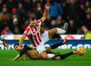 Erik Pieters of Stoke City is tackled by Mathieu Flamini of Arsenal during the Barclays Premier League match between Stoke City and Arsenal at Britannia Stadium on January 17, 2016 in Stoke on Trent, England.  (Photo by Laurence Griffiths/Getty Images)