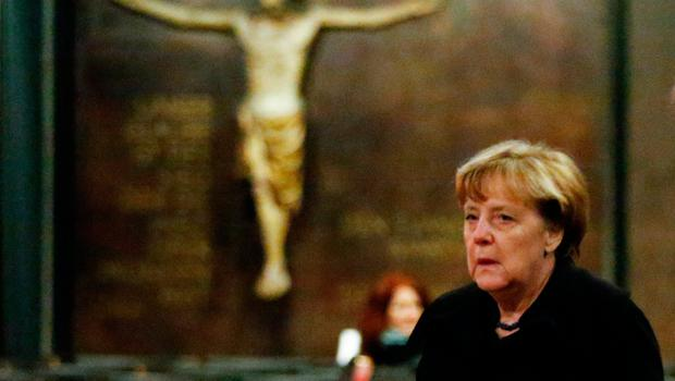 """German Chancellor Angela Merkel arrives to sign the book of condolences on December 20, 2016 inside the Kaiser-Wilhelm-Gedaechtniskirche (Kaiser Wilhelm Memorial Church), the day after an attack at the nearby Christmas market in central Berlin.  German police said they were treating as """"a probable terrorist attack"""" the killing of 12 people when the speeding lorry cut a bloody swath through the packed Berlin Christmas market. / AFP PHOTO / POOL / HANNIBAL HANSCHKEHANNIBAL HANSCHKE/AFP/Getty Images"""
