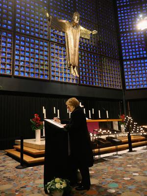 BERLIN, GERMANY - DECEMBER 20: German Chancellor Angela Merkel signs a book of condolences at the Kaiser Wilhelm Memorial Church the day after a truck drove into an adjacent, crowded Christmas market on December 20, 2016 in Berlin, Germany. So far 12 people are confirmed dead and 45 injured. Authorities have confirmed they believe the incident was an attack and have arrested a Pakistani man who they believe was the driver of the truck and who had fled immediately after the attack. Among the dead are a Polish man who was found on the passenger seat of the truck. Police are investigating the possibility that the truck, which belongs to a Polish trucking company, was stolen yesterday morning.  (Photo by Sean Gallup/Getty Images)