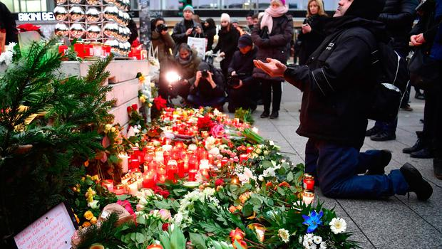 A Muslim mam prays at a makeshift memorial for the attack victims, on December 20, 2016 in front of the Kaiser-Wilhelm-Gedaechtniskirche (Kaiser Wilhelm Memorial Church) in Berlin, where a truck crashed into a Christmas market. Twelve people were killed and almost 50 wounded, 18 seriously, when the lorry tore through the crowd on December 19, 2016, smashing wooden stalls and crushing victims, in scenes reminiscent of July's deadly attack in the French Riviera city of Nice. / AFP PHOTO / John MACDOUGALLJOHN MACDOUGALL/AFP/Getty Images