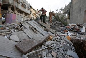 A Palestinian walks on the rubble from a damaged house following an overnight Israeli missile strike in Gaza City, Tuesday, July 15, 2014. Egypt presented a cease-fire plan Monday to end a week of heavy fighting between Israel and Hamas militants in the Gaza Strip that has left at least 185 people dead, and both sides said they were seriously considering the proposal.The late-night offer by Egypt marked the first sign of a breakthrough in international efforts to end the conflict. (AP Photo/Lefteris Pitarakis)