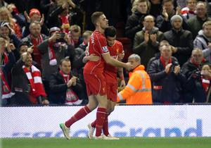 Liverpool's Philippe Coutinho (right) celebrates with team mate Jordan Henderson (left) after scoring his sides first goal of the game during the Barclays Premier League match at Anfield, Liverpool. Peter Byrne/PA Wire.