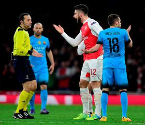 Arsenal's French striker Olivier Giroud (C) gestures as he speaks to Turkish referee Cuneyt Cakir (L) following a challenge by Barcelona's defender Jordi Alba during the UEFA Champions League round of 16 1st leg football match between Arsenal and Barcelona at the Emirates Stadium in London on February 23, 2016.   / AFP / JAVIER SORIANOJAVIER SORIANO/AFP/Getty Images