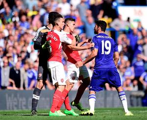 """Arsenal's Gabriel Paulista (centre) and Chelsea's Diego Costa exchange words during the Barclays Premier League match at Stamford Bridge, London. PRESS ASSOCIATION Photo. Picture date: Saturday September 19, 2015. See PA story SOCCER Chelsea. Photo credit should read: Adam Davy/PA Wire. RESTRICTIONS: EDITORIAL USE ONLY No use with unauthorised audio, video, data, fixture lists, club/league logos or """"live"""" services. Online in-match use limited to 45 images, no video emulation. No use in betting, games or single club/league/player publications."""