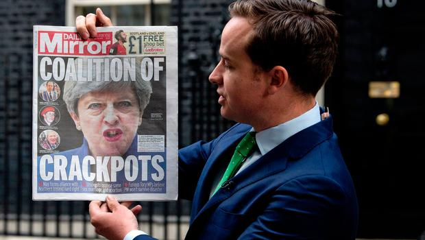 "A television presenter stands outside 10 Downing Street in London on June 10, 2017, holding a copy of The Daily Mirror newspaper with the headline ""Coalition of Crackpots"" the day after the general election resulted in a hung parliament and British Prime Minister Theresa May forming a minority government. AFP/Getty Images"