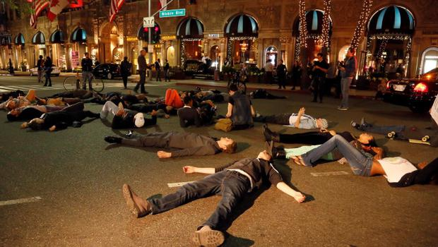 Protesters lay down on a street in Beverly Hills, Los Angeles, Calf., Tuesday, Nov. 25, 2014, after the announcement of the grand jury decision not to indict Ferguson police officer Darren Wilson in the fatal shooting of Michael Brown, an unarmed 18-year-old. (AP Photo/Nick Ut)
