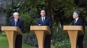 Prime Minister David Cameron (centre) talks as Northern Ireland's Deputy First Minister Martin McGuinness (left) and Northern Ireland's First Minister Peter Robinson (right) listen during a press conference in the garden of 10 Downing Street in central London. PRESS ASSOCIATION Photo. Picture date: Friday June 14, 2013. An economic pact to help Northern Ireland's struggling economy will be agreed at Westminster. Initiatives to stimulate private sector investment and job creation, boost lending to businesses and deliver capital funding for frontline projects such as hospitals, schools and roads are expected to be included in the package which will be announced at Downing Street. Mr Cameron said the ambitious package would help strengthen the foundations for peace and send a positive message ahead of next week's G8 summit at Lough Erne. See PA story ULSTER Economy. Photo credit should read: Will Oliver/PA Wire
