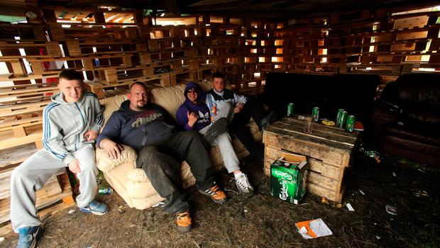 Bonfire builders take a rest  in the New Mosley area of Belfast. Niall Carson/PA Wire.