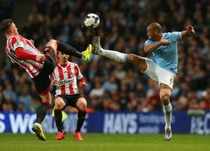 Connor Wickham of Sunderland and Vincent Kompany of Manchester City battle for the ball  during the Barclays Premier League match between Manchester City and Sunderland at Etihad Stadium on April 16, 2014 in Manchester, England.  (Photo by Alex Livesey/Getty Images)