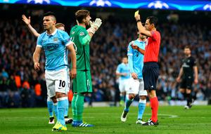 MANCHESTER, ENGLAND - APRIL 12:  Referee Carlos Velasco Carballo shows a yellow card to goalkeeper Kevin Trapp of Paris Saint-Germain after he fouls  Sergio Aguero of Manchester City (10) during the UEFA Champions League quarter final second leg match between Manchester City FC and Paris Saint-Germain at the Etihad Stadium on April 12, 2016 in Manchester, United Kingdom.  (Photo by Clive Brunskill/Getty Images)