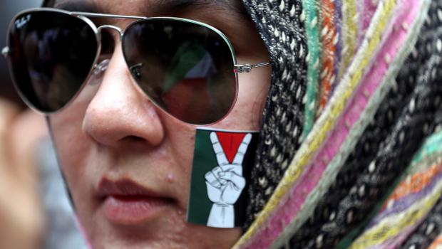 A Thai-Muslim activist puts a sticker on her face during a rally outside the Israeli embassy in Bangkok, Thailand Tuesday, July 15, 2014. Several hundreds of activists took part in the rally to show solidarity for Palestine against Israel's attacks on Gaza. (AP Photo/Apichart Weerawong)