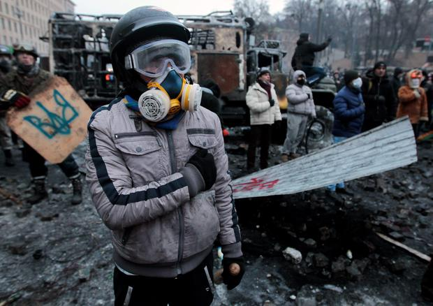Pro-European Union activists sing the national anthem during unrest, in central Kiev, Ukraine, Tuesday, Jan. 21, 2014. Anti-government protesters have held their ground through a night of violent street clashes in the Ukrainian capital, despite police moving in to dismantle barricades erected in a street leading to government offices. Police attempted to move in on the protest camp early Tuesday, but faced fierce resistance from demonstrators who tossed fire bombs and stones in their direction. (AP Photo/Sergei Chuzavkov)