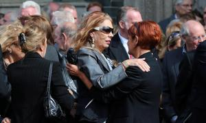 Christine Anderson (left) is comforted during the funeral of her husband BBC broadcaster Gerry Anderson at St Eugene's Cathedral in Londonderry. PRESS ASSOCIATION Photo. Picture date: Sunday August 24, 2014. See PA story FUNERAL Anderson. Photo credit should read: Niall Carson/PA Wire