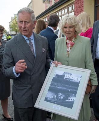 """Britain's Prince Charles, Prince of Wales (L) and his wife Camilla, Duchess of Cornwall (R) hold a photograph of the boat Shadow V, the boat on which the prince's great-uncle Lord Mountbatten was killed in an IRA bombing in 1979,  presented to the prince by Pat Markeyira during a visit to the village of Mullaghmore in Ireland on May 20, 2015 the scene of the 1979 bomb. Britain's Prince Charles spoke of his """"anguish"""" at the murder of his godfather by IRA paramilitaries in 1979 as he became the first royal to visit the assassination site in Ireland.  Charles remembered Lord Louis Mountbatten as """"the grandfather I never had"""" on an emotional trip to the rugged coastline, saying he understood the suffering of the Irish people in """"a profound way"""".  Peter McHugh helped with the rescue effort in the aftermath of the 1979 attack.  AFP PHOTO / POOL / ARTHUR EDWARDSARTHUR EDWARDS/AFP/Getty Images"""