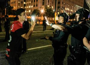 """A protester (L) confronts police as demonstrators shut down the 101 Freeway, a major thoroughfare in the city, following a rally to protest a day after President-elect Donald Trump's election victory in Los Angeles, California, late on November 9, 2016. Protesters burned a giant orange-haired head of Donald Trump in effigy, lit fires ins the streets and blocked traffic lanes late on November 9 as rage over the billionaire's election victory spilled onto the streets of US cities. From New York to Los Angeles, thousands of people in around 10 cities rallied against the president-elect a day after his stunning win, some carrying signs declaiming """"Not our President"""" and """"Love trumps hate."""" / AFP PHOTO / RINGO CHIURINGO CHIU/AFP/Getty Images"""