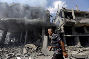 A Palestinian man walks by buildings heavily damaged by Israeli strikes in Beit Hanoun, northern Gaza Strip, Saturday, July 26, 2014.  (AP Photo/Lefteris Pitarakis)