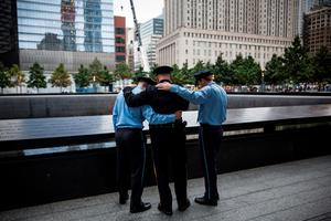 NEW YORK, NY - SEPTEMBER 11:  (L-R) Zachary Ellicott, a firefighter in Stanhope, NJ, Mitch Ellicott, a lieutenant with the Sussex County Sherrif's office and father to Zach and Benjamin, and Benjamin Ellicott, a firefighter in Stanhope, NJ, take a moment to remember a family member lost in the terrorist attack of September 11, 2001, on September 11, 2015 in New York City. Today marks the 14th anniversary of the attacks where nearly 3,000 people were killed in New York, Washington D.C. and Pennsylvania.  (Photo by Andrew Burton/Getty Images)