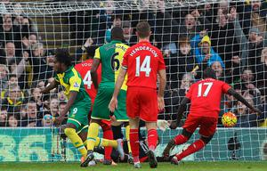 Norwich City's Congolese striker Dieumerci Mbokani (L) turns to celebrate after scoring their first goal during the English Premier League football match between Norwich City and Liverpool at Carrow Road in Norwich, eastern England, on January 23, 2016. AFP PHOTO / LINDSEY PARNABY  RESTRICTED TO EDITORIAL USE. No use with unauthorized audio, video, data, fixture lists, club/league logos or 'live' services. Online in-match use limited to 75 images, no video emulation. No use in betting, games or single club/league/player publications.LINDSEY PARNABY/AFP/Getty Images