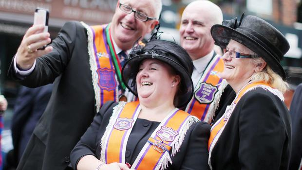 Press Eye - Belfast -  Northern Ireland - 13th July  2015  Belfast's Orange Order annual 12th of July demonstration makes its way through the City Centre to the field at Malone House beside Shaws Bridge.  Glasgow County Lodge members(L-R) Mark Kirkland, Eddie McGonnell, Kirsty Gardner and Gina McNee pose for a selfie as the parade takes a break on the Lisburn Road.   Picture by Jonathan Porter/Press Eye