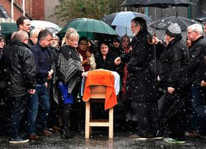 Sinn Fein President Gerry Adams (R) and Northern Ire;and Leader, Michelle O'Neill (L) adjusts an Irish flag on the coffin of the late Martin McGuinness watched by his wife Bernadette McGuinness (C) on March 21, 2017 in Derry (Photo by Charles McQuillan/Getty Images)