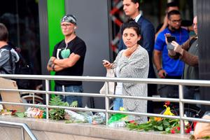 A woman stands near a mall where a shooting took place leaving nine people dead the day before on Saturday, July 23, 2016 in Munich, Germany. (AP Photo/Kerstin Joensson)