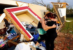 Alli Christian, left, returns Jessica Wilkinson's dog Bella to her after finding the pet amid the wreckage of Wilkinson's home shortly after a tornado struck near 156th street and Franklin Road on Sunday, May 19, 2013, in Norman, Okla. No one was in the home when the storm struck.  (AP Photo/The Oklahoman, Steve Sisney)