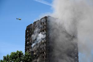 LONDON, ENGLAND - JUNE 14:  A heicopter circles as smoke rises from the building after a huge fire engulfed the 24 story Grenfell Tower in Latimer Road, West London in the early hours of this morning on June 14, 2017 in London, England.  The Mayor of London, Sadiq Khan, has declared the fire a major incident as more than 200 firefighters are still tackling the blaze while at least 30 people are receiving hospital treatment.  (Photo by Carl Court/Getty Images)