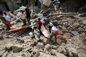 Palestinian medics remove a dead body found under the rubbles of a home destroyed by an Israeli strike in the Shajaiyeh neighborhood of Gaza City, northern Gaza Strip, Sunday, July 20, 2014.  (AP Photo/Hatem Moussa)
