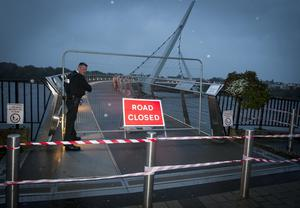 PEACE BRIDGE CLOSED. . . . .A PSNI officer braves the elements to secure the Peace Bridge in Derry/Londonderry last night. The footbridge between the cityside and waterside was closed around 6.15pm as winds increased. (Photo: Jim McCafferty Photography)