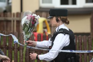 PRESS EYE BELFAST - 19/4/19-  PSNI officer receives floral tributes left by members of the public  following the murder of 29-year-old Lyra McKee during rioting after police searches in the area last night.