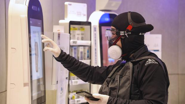 A shopper wearing goggles with a face mask and gloves uses a self checkout machine at a supermarket in Wuhan (Chinatopix via AP)